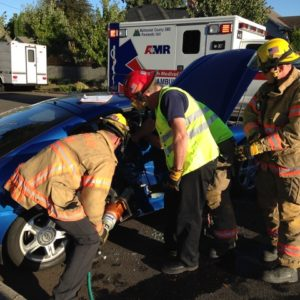 Paramedics and firefighters wearing safety vests assisting victims on a car accident. Portland Lawyer car accident, personal injury, victim of a drunk driver, hit and run