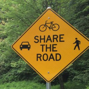 Diamond shape traditional Share the Road yellow sign showing a car, bicycle and a person walking black icons with dense forest vegetation on the back. Accidents, assault & Battery, Drunk driver, Lawyer questions answered