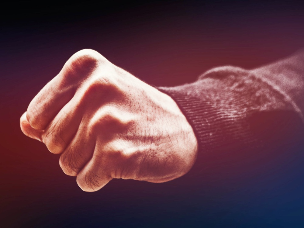 Closed fist in a dark background. Portland lawyer assault and Battery lawyer civil justice
