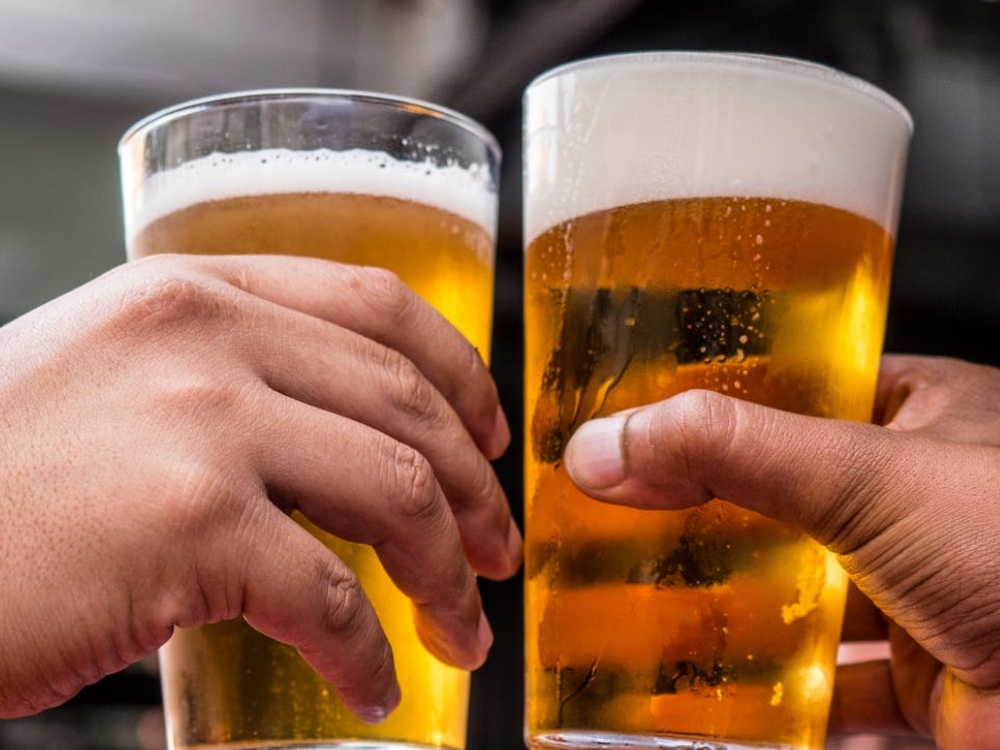hands holding two glasses of beer. Driving under the influence lawyer, accident lawyer portland